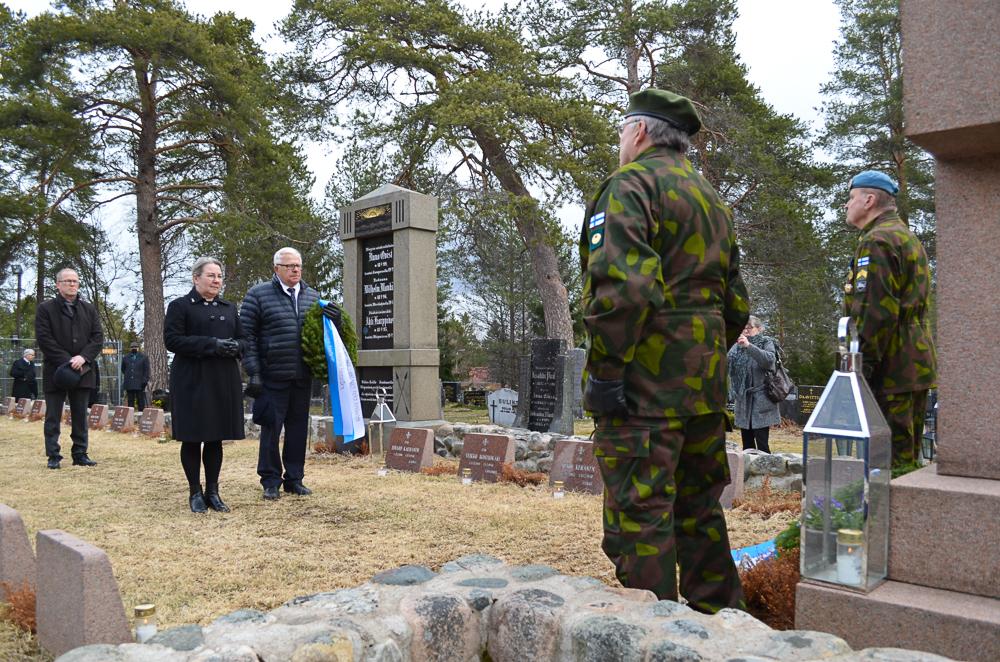 Seurakunnan ja kunnan yhteistä seppelettä ovat laskemassa valtuuston puheenjohtaja Pia Hanski, kirkkoneuvoston jäsen Taavi Jarva sekä kappalainen Vesa äärelä. Jarva ja Hanski ovat pysähtyneet muistomerkin eteen ja Jarva pitää kädessään seppelettä. Äärelä seisoo taaempana.