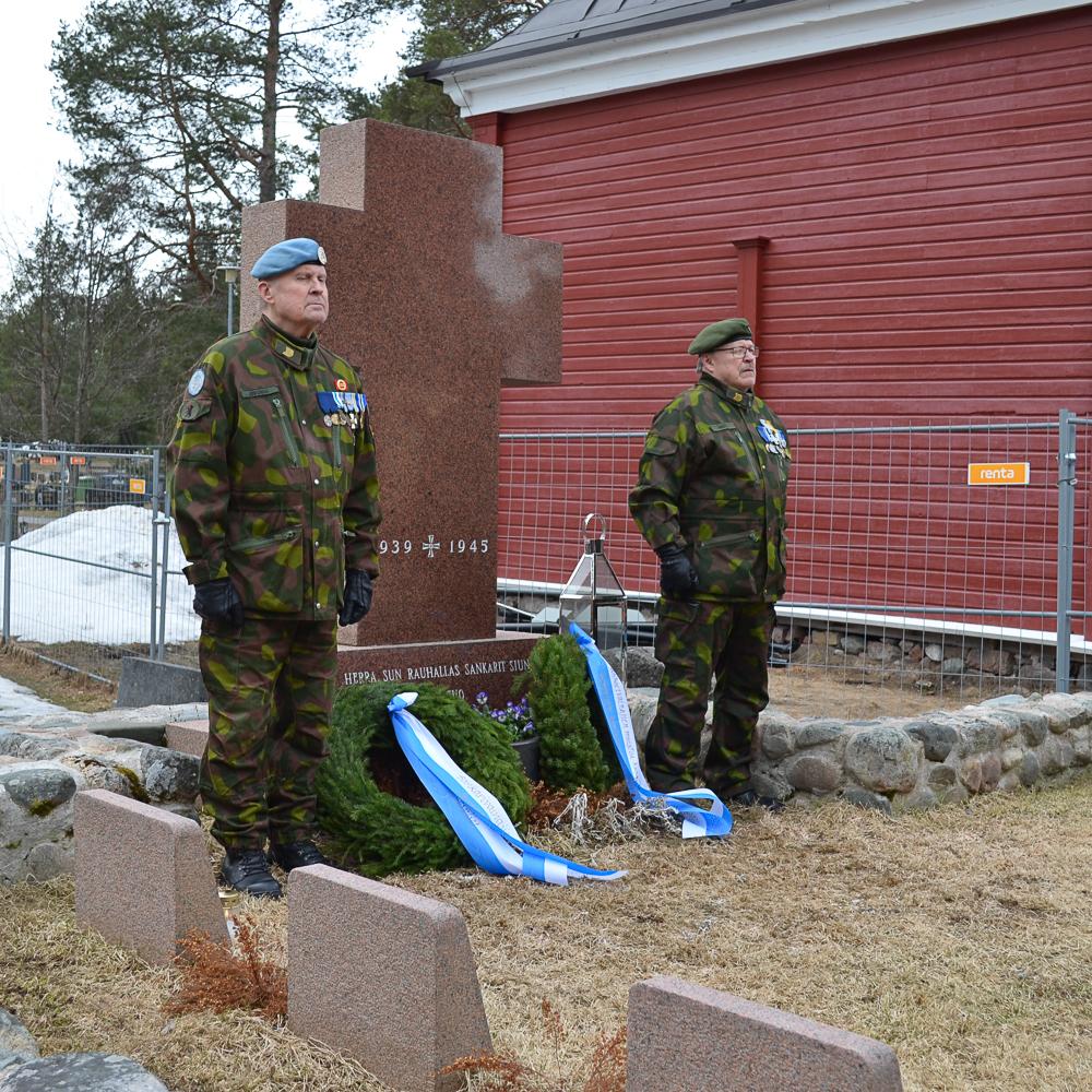 Sotaveteraanien muistomerkillä seisoi tilaisuuden ajan vartiossa Kempeleen reserviläiset ry:n Risto Juvonen ja Kari Pentti. Ristin muotoisen muistomerkin juurelle laskettiin kaksi seppelettä. Taustalla näkyy merkkejä Kempeleen vanhan kirkon työmaasta.