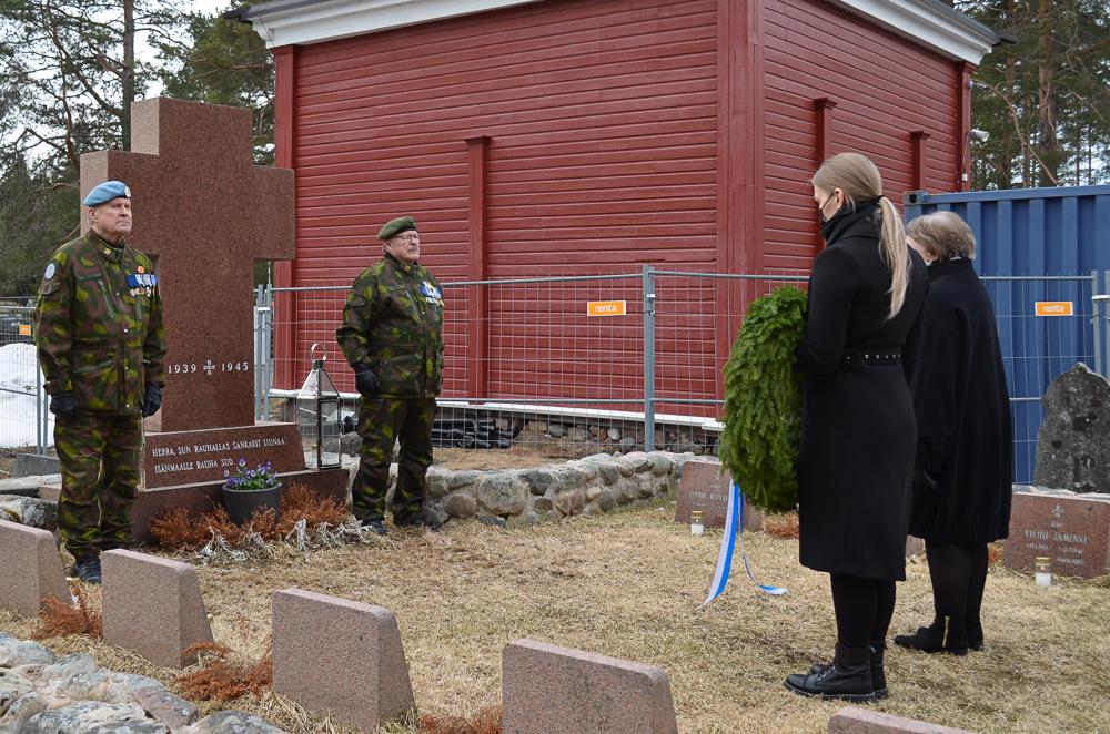 Reserviläisten liiton seppeleen laskivat Kempeleen seurakunnan Anna Keränen ja Kempeleen kirkkovaltuuston puheenjohtaja Kaisu Juvani. Naiset ovat pysähtyneet parin metrin päähän muistomerkistä hiljaisuudessa, Keränen pitää seppelettä kädessään.